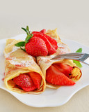 Crepes with strawberries sprinkled with powered sugar