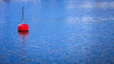 Single red buoy on calm blue sea surface