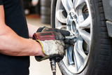Fototapety removing bolt from a wheel  using pneumatic gun, tire replacement