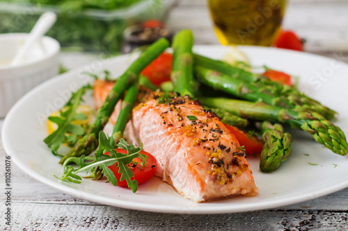 Baked salmon garnished with asparagus and tomatoes with herbs - 110261076