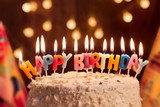 Fototapety Birthday cake with candles, bright lights bokeh.Celebration.