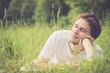 Junger Mann liegt im Gras, nachdenklich
