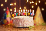 Fototapety Birthday cake with candles, bright lights bokeh.