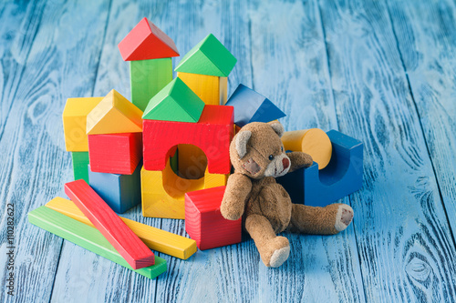 Plakát shot of pile of various wooden blocks and toy bear