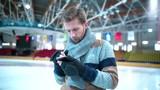 Young man with phone at skating rink
