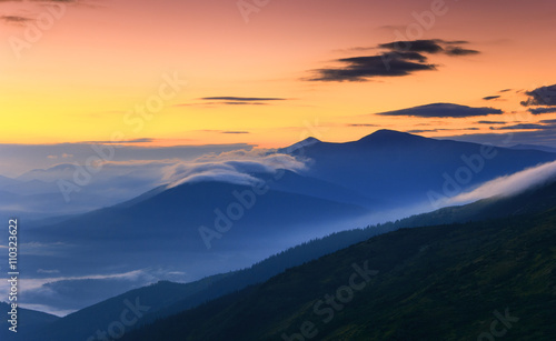 Poster Oranje eclat Sunrise landscape of foggy and cloudy mountain valley.