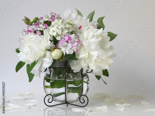 Fototapeta Bouquet of white peony flowers in a vase. Floral decoration with bouquet of peonies and pink carnations flowers in a vase.