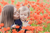 Mother with funny child outdoor at poppy flowers field