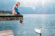 Father with son sit on wooden pier and look on white swan swims