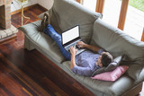 Young man lying comfortably on the sofa while using the laptop w