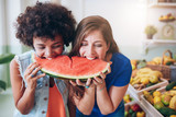Two young woman eating watermelon and having fun