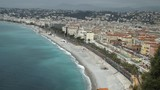Mediterranean country with amazing sea and promenade with walking people. On the beach working men and vehicles.