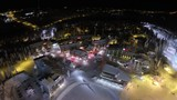 Aerial view of ski centre area at night. Illuminated hotels and slopes in the pinery. Winter recreation