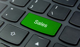 Business Concept: Close-up the Sales button on the keyboard and have Lime, Green color button isolate black keyboard