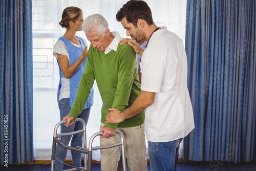 Poster Nurse helping seniors walking with a walker