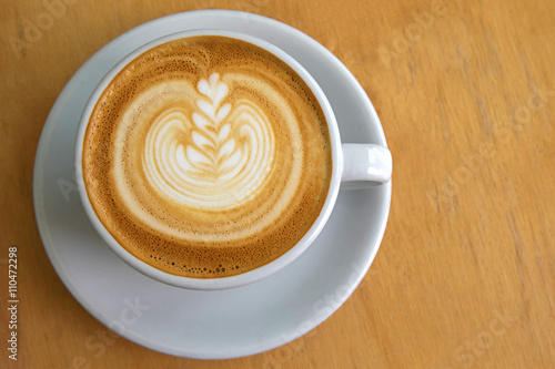 Papiers peints Cafe White cup of hot coffee with Latte Art decoration on the surface, a wooden table