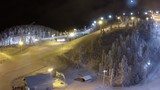Aerial view of ski centre at night. Illuminated slopes in the pinery and working ski-lift. Winter recreation