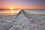 Długie drewniane groiny na plaży, zachód słońca nad morzem