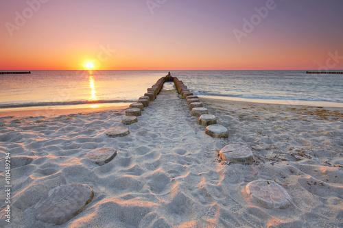 Fototapeta lange hölzerne Buhnen am Strand, Sonnenuntergang am Meer