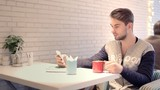 Young man with smartphone sitting in cafe