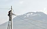 elettricista uomo al lavoro, su scala con palo e cavi