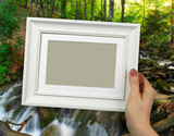 Wooden frame in woman hands. Waterfall on the background