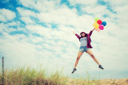 Póster Hermosa muchacha que salta con los globos en la playa