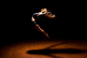 Beautiful dancer jumping in a stage