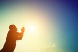 Silhouette of man praying at sunrise.