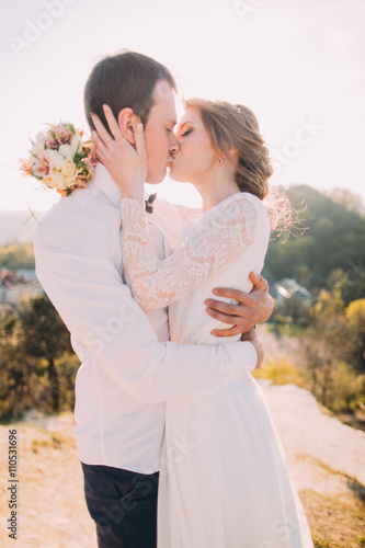 Poster Luxury happy bride and stylish groom kissing on background of sunny mountains