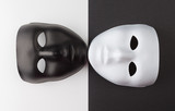 Black and white masks touching chins on contrasting backgrounds, Personality change theatrical concept