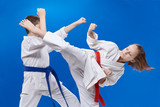 A circular punch and block are training boy and girl