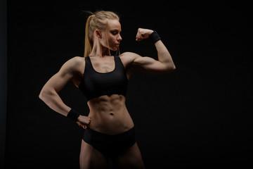 Young muscular woman posing on black © Anton Gvozdikov