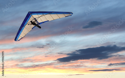 Fototapeta Hanglider - Hanglider Flying over the ocean at sunset