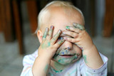 Funny one year old girl covering messy painted face with her dirty little hands