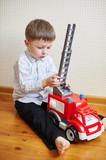 little boy playing red toy machine in room