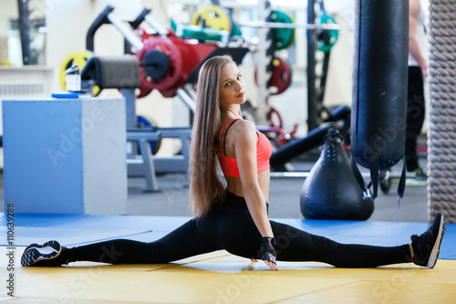 Fototapeta Beautiful young girl engaged fitness in the gym.