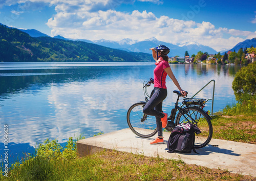 Poszter woman with e-bike enjoying view over lake