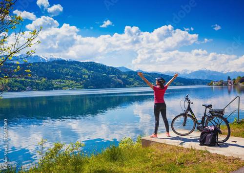 Poster Femme avec e-bike profitant vue sur le lac-lac et vélo 02