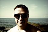 Мужчина на пляже в солнечный очках