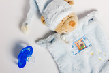 Baby bottles, pacifiers and toys lying on a white background.