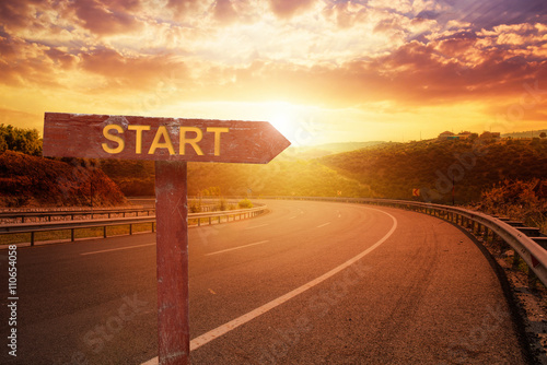 Start Direction on sunset over asphalt road Poster