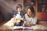 Young mother, read a book to her child, boy in the living room o