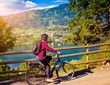 woman with e-bike cycling beside a beautiful lake-lake and bike
