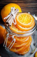 Candied oranges in glass jar, cinnamon sticks