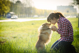 Young woman sitting with her dog sheltie on the grass and playing with the shetland sheepdog