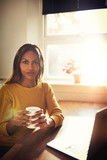 Calm woman holding coffee near bright window
