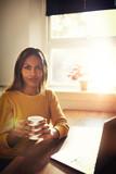 Calm woman holding coffee near bright window