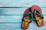 Thongs with flag of Sri Lanka, on blue wooden boards