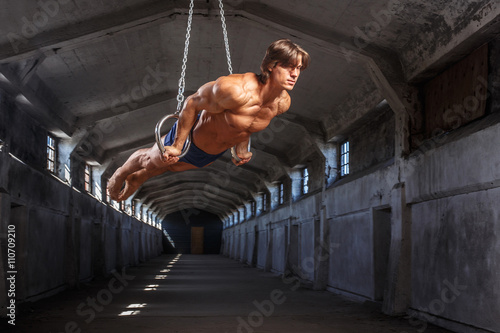 Man workouts in the air with gimnastic rings. Plakát